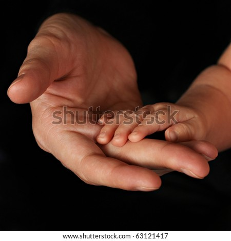 A young infant hand in hand with father. - stock photo
