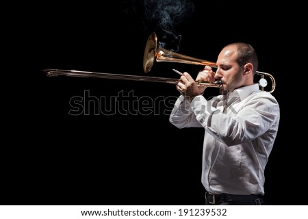 a young jazzer with a trombone over black background - stock photo