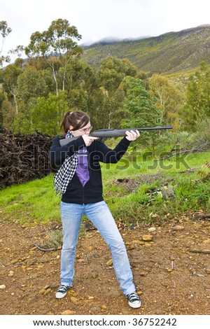A young lady busy aiming an airgun at a target. - stock photo