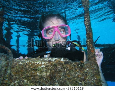 A young lady diver deep underwater on a shipwreck dive site - stock photo