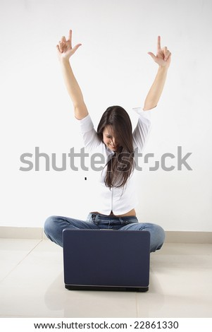 A young lady with a computer with arms raised. - stock photo