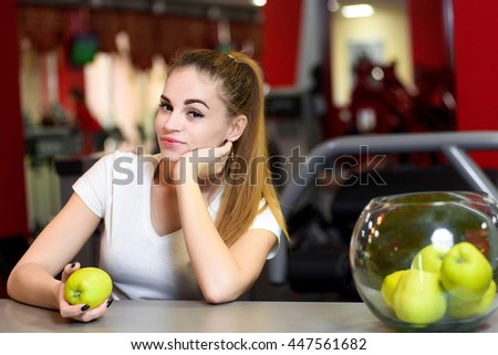 A young lady with an apple in her hand smiling attractively to the camera - stock photo