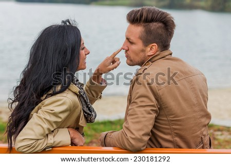 a young, laughed liebtes couple sitting on a park bench - stock photo