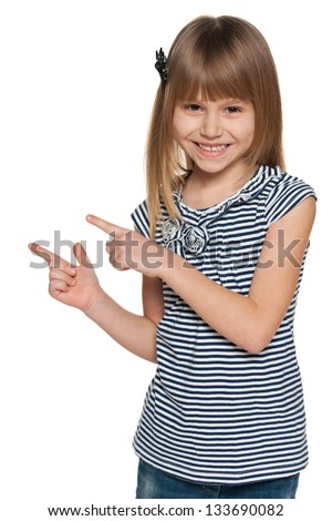 A young laughing girl shows her fingers to the side - stock photo