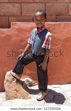 A young little boy with his foot on the rock being photographed in formal clothing. - stock photo