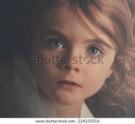 A young little child is looking into the camera with a serious expression. The closeup of the girl shows her hair and blue eyes for a beauty or innocence concept. - stock photo