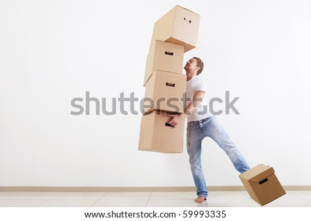 A young-looking man trying to carry all the boxes - stock photo
