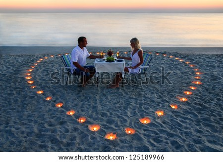 A young lovers couple share a romantic supper with candles heart on the sea beach - stock photo