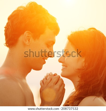 A young  loving  couple hugging and kissing on the beach at sunset. Two lovers, man and woman near the water. Summer in love  - stock photo
