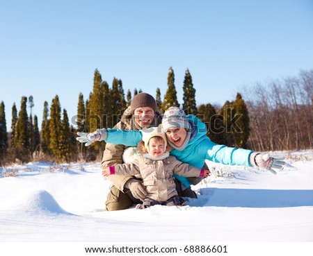 A young loving family enjoying vacation in snow - stock photo