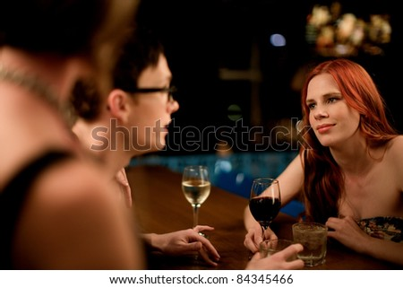 A young male and female couple, talking over casual drinks with a third person out of focus in the foreground.