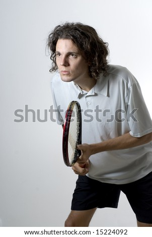 A young male athlete holding a tennis racket. Vertically framed shot. - stock photo