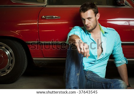 A young male fashion model in-front of a vintage car. - stock photo
