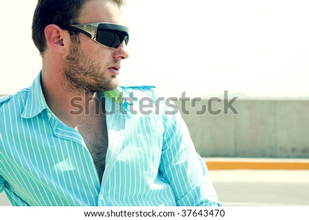 A young male fashion model wearing glasses in a car park. - stock photo