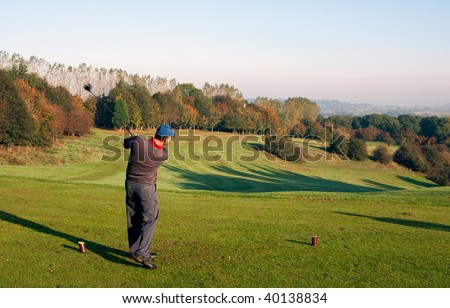 A young male golfer teeing off on an autumn morning on a golf course in England. Motion blur on the clubhead and flying golf ball. - stock photo