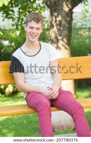 A young male model is smiling at the camera and sitting relaxedly on a beautiful wooden bench in a green garden - stock photo