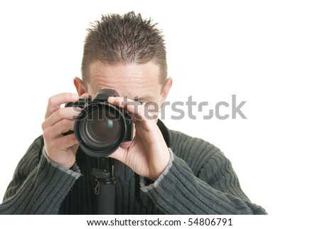 A young male photographer holds his camera - stock photo