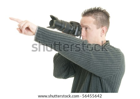 A young male photographer points while holding his camera - stock photo