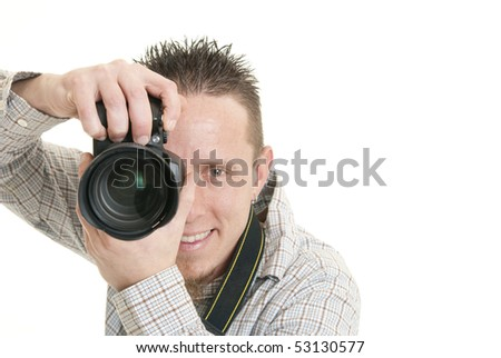 A young male photographer smiles while holding his camera - stock photo
