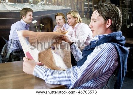 a young male reading his newspaper in a restaurant with other customers discussing on the background - stock photo