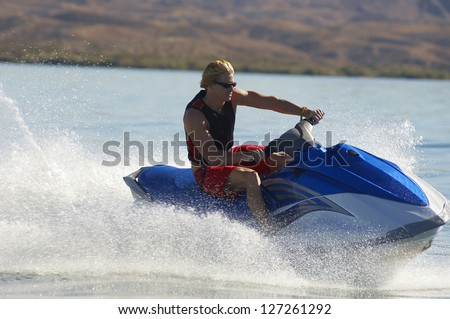 A young male riding jet ski at lake on sunny day - stock photo