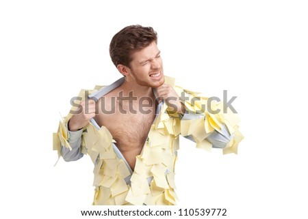 A young male ripping off his shirt, covered with stickers, isolated on white on white - stock photo
