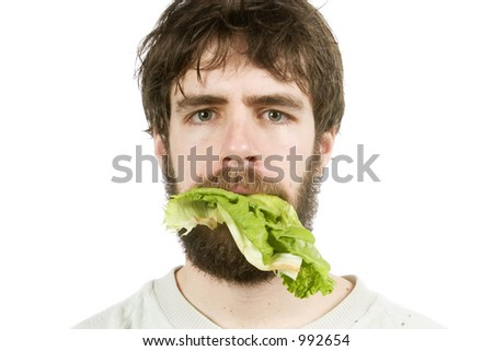 A young male with lettuce in his mouth, looking unimpressed. - stock photo
