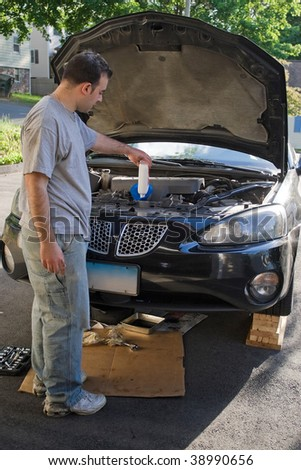 A young man adding oil to his car at the end of an oil change. - stock photo