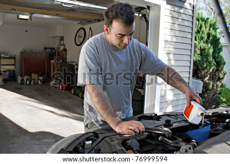 A young man adding oil to his cars engine at the end of an oil change. - stock photo