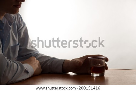 A young man alcohol abuse, on the table is alcohol - stock photo