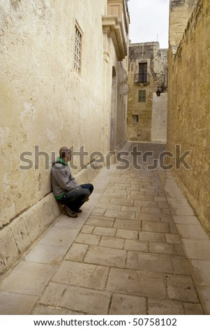 A young man, alone on a deserted street - stock photo