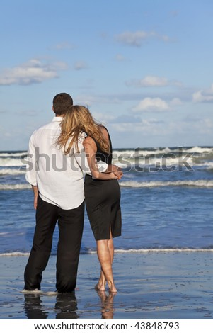 A young man and woman embracing as a romantic couple on a beach with a bright blue sky