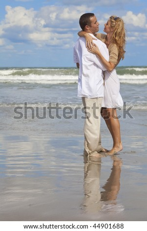 A young man and woman embracing as a romantic couple on a beach with a bright blue sky - stock photo