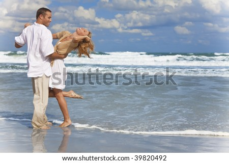 A young man and woman having fun dancing as a romantic couple on a beach with a bright blue sky - stock photo