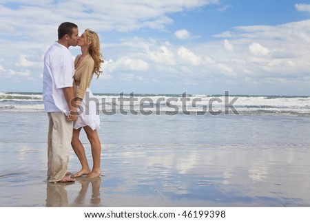 A young man and woman holding hands and kissing as a romantic couple on a beach