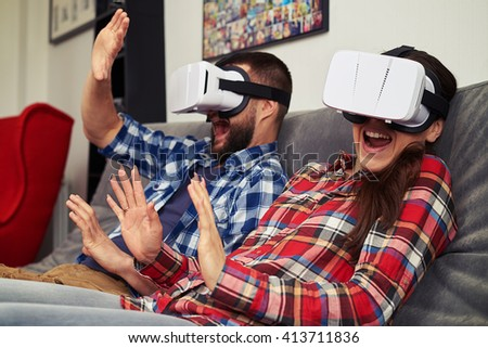 A young man and woman in casual clothes and virtual reality glasses shocked by what they see in virtual reality - stock photo