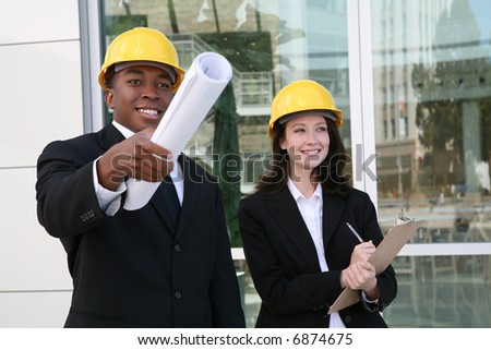 A young man and woman working as  architects on a construction site - stock photo