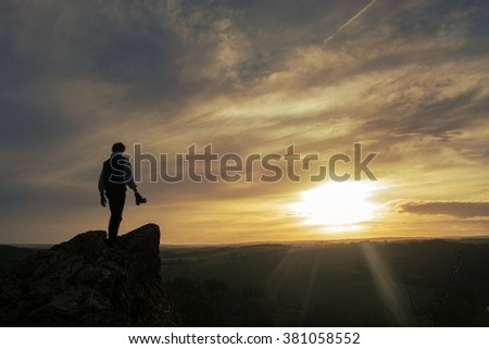 A young man atop a rock at sunset