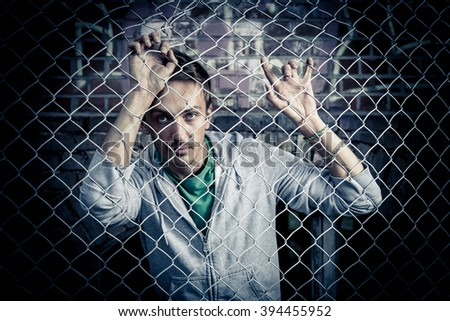 a young man behind bars close - stock photo