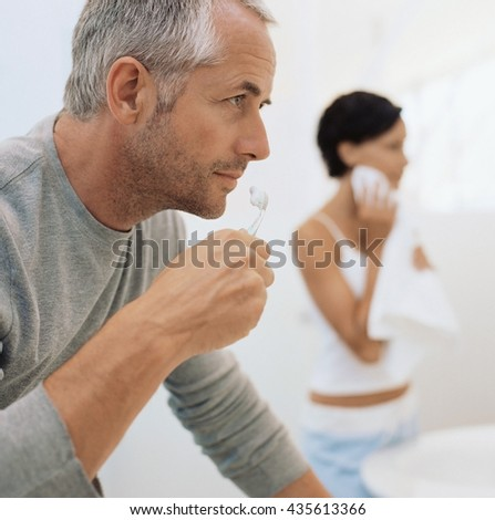 A young man brushing his teeth - stock photo