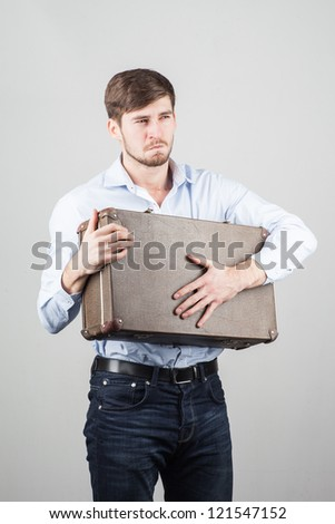 A young man carrying a suitcase - stock photo