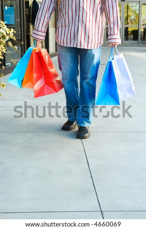 A young man carrying shopping bags at an outdoor shopping mall - stock photo