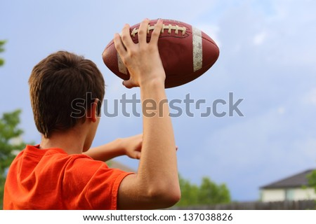 A young man cocking his arm back and getting ready to throw a football - stock photo