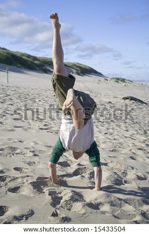 A young man doing a handstand on the beach - stock photo