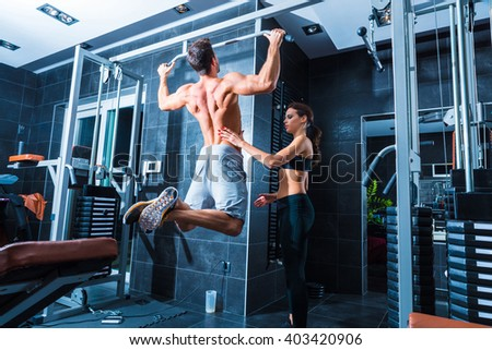 A young man doing pull ups in the Gym. - stock photo