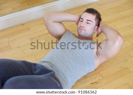 A young man doing sit ups - stock photo