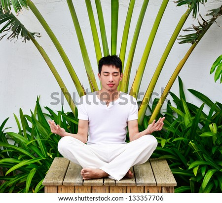 A young man doing yoga in Nature sitting wooden chair - stock photo