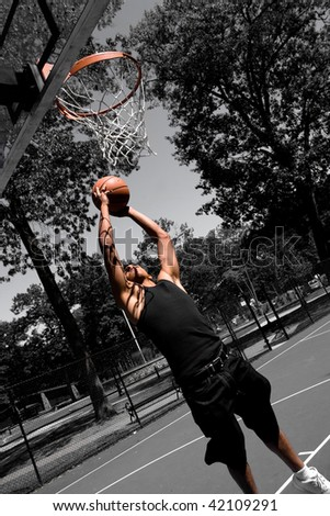 A young man driving to the basketball hoop for a dunk with selective color. - stock photo