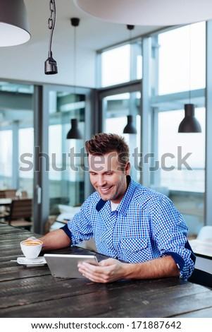 A young man enjoying a cup of coffee and surfing the internet - stock photo