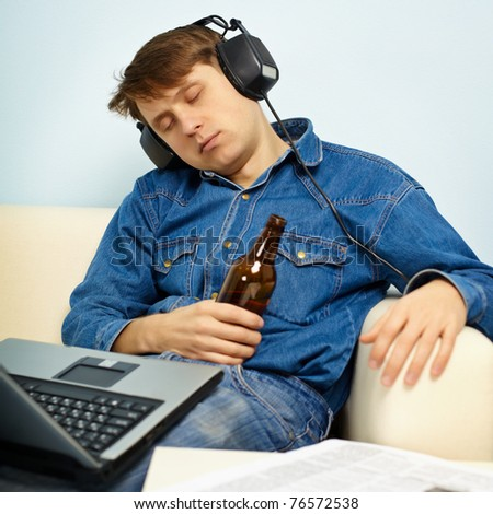 A young man fell asleep at home on the couch with a beer - stock photo